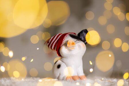 Decorative Christmas-themed figurines. Cute pig in a hat. Christmas tree decoration. Festive decor, warm bokeh lights
