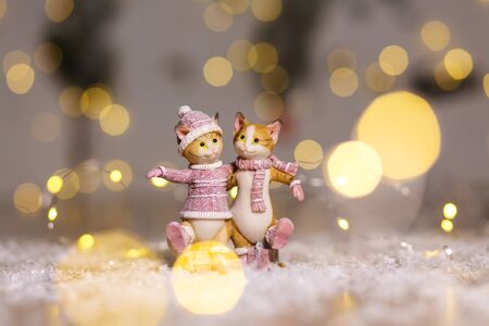 Decorative figurines of a Christmas theme. Figurine of cute hugging cats dressed in a knitted sweater, scarf and hat. Christmas tree decoration. Festive decor, warm bokeh lights Imagens