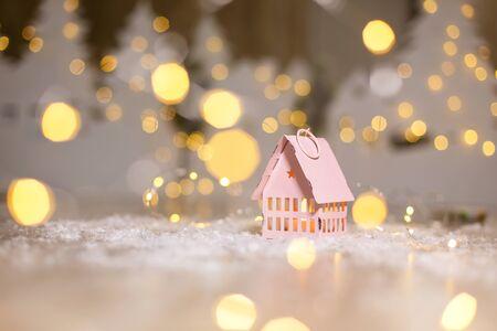Decorative Christmas-themed figurines. Little toy house, Christmas tale. Christmas tree decoration. Festive decor, warm bokeh lights