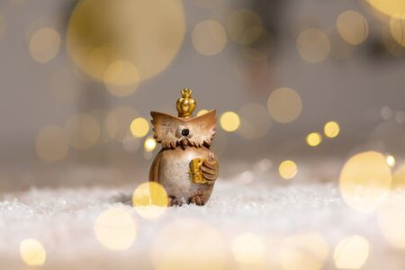 decorative figurine toy owl with a golden crown on his head. Festive decor, warm bokeh lights. Archivio Fotografico