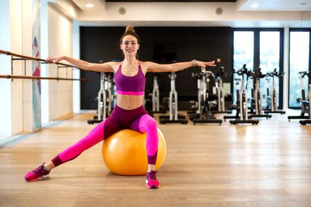 Young woman in sportwear sport exercise wit yellow fitball in gym. Fitness and wellness lifestyle concept.
