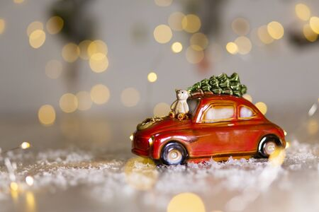 Decorative figurines of a Christmas theme. A statuette of a red car on which a teddy bear sits. Christmas tree decoration. Festive decor, warm bokeh lights
