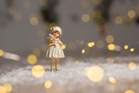 Decorative Christmas-themed figurines. Statuette girl. Christmas tree decoration. Festive decor, warm bokeh lights