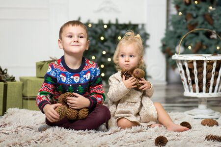girl and boy playing on the floor with cones to decorate the Christmas tree. brother and sister near the Christmas tree and boxes with Christmas gifts. Merry Christmas and happy holidays.