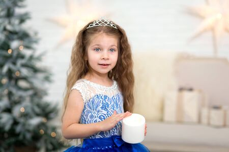 Cute little girl holding an artificial candle in her hands for home decoration for the Christmas holidays. Child-friendly scenery.