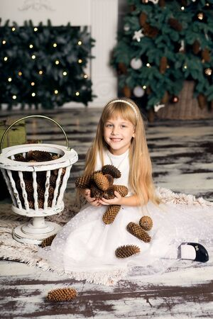 little girl in a white dress plays with pine cones in Christmas decorations against the background of the Christmas tree and fireplace. Merry Christmas and happy New Year.