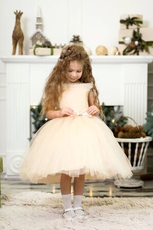 Cute little girl in a lush beige dress posing near the Christmas tree Stock Photo