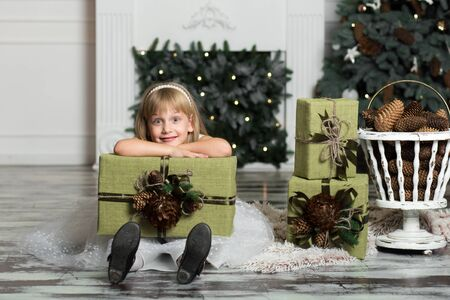 Happy girl holding a big box with a gift over her head. winter holidays, christmas and people concept