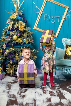 Cute little girl and boy are smiling and holding gifts under the Christmas tree. Brother and sister unpack gift boxes on Christmas eve