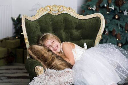 Little girl pretending to be sleeping on an armchair near a Christmas tree to meet Santa when he brings presents.