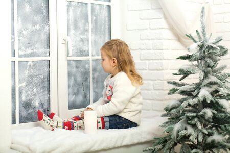 Little girl sitting on the windowsill in the evening before Christmas. A cozy romantic getaway in winter. The concept of Merry Christmas, New Year, holiday, winter, childhood.