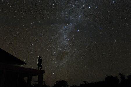 alone woman on rooftop watching mliky way and stars in the night sky on Bali island Standard-Bild