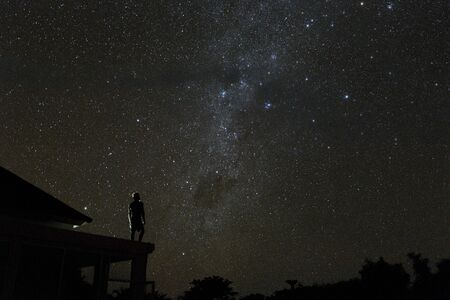 alone woman on rooftop watching mliky way and stars in the night sky on Bali island Banque d'images