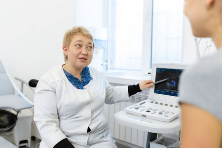 the doctor advises the patient's girl after an ultrasound diagnosis. indicates with a pen on the monitor of the ultrasound machine the problematic place to which the patient should pay special attention. 版權商用圖片