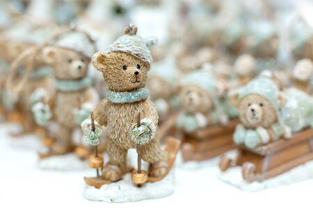 Decorative figurines of a Christmas theme. Statuette of a teddy bear on a wooden sleigh. Christmas tree decoration. Festive decor, warm bokeh lights