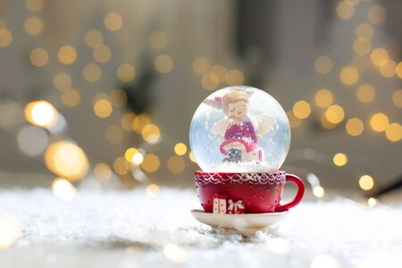 Decorative figurines of a Christmas theme. Glass ball with snowflakes, inside which sits a Christmas angel. The ball lies in a red cup. Festive decor, warm bokeh lights