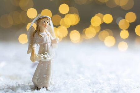 Decorative Christmas-themed figurines. Statuette of a Christmas angel. Christmas tree decoration. Festive decor, warm bokeh lights