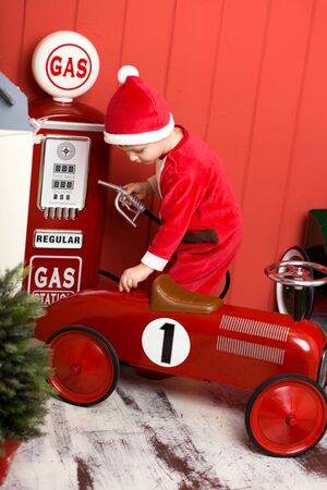 Little boy in santa costume rides a toy red car. Happy childhood. Christmas Eve