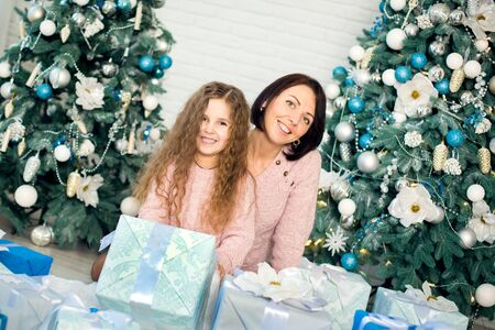 Family celebrates Christmas. Cozy christmas morning. Mommy and daughter wrapping gifts to put under the christmas tree. Gift boxes. Merry Christmas and happy holidays. Happy childhood.