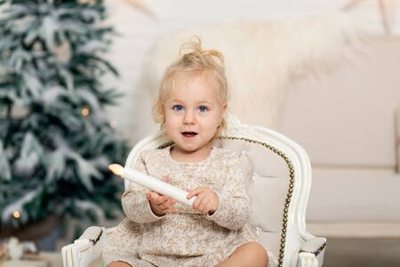 A little girl sits In the armchair and holds a candle in her hand in a room near the Christmas tree.