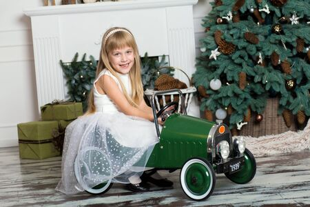 little girl in a white dress rides a vintage childrens car in Christmas decorations against the background of a Christmas tree and a fireplace. Happy New year and merry Christmas.