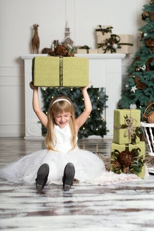 Happy girl holding a big box with a gift over her head. winter holidays, christmas and people concept.