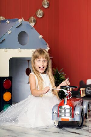 Cute little girl is playing with a big toy fire truck. Happy childhood Stock Photo