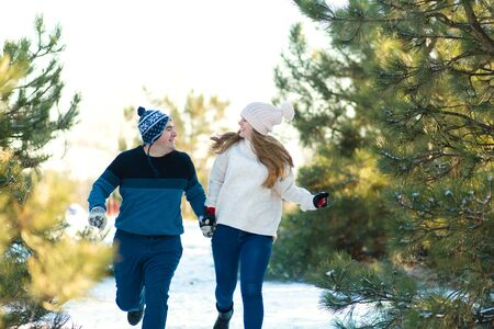 A loving couple holding hands runs through the winter forest. Laugh and have a good time.