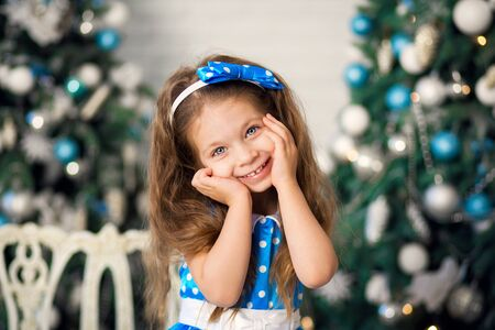 Cute little girl with a Christmas present, in a blue dress sits next to decorated Christmas trees. New Year, Christmas family holiday. Stock Photo