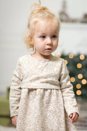 Portrait of a little girl with blonde hair in a photo of a Christmas tree and New Years decor on the eve of Christmas