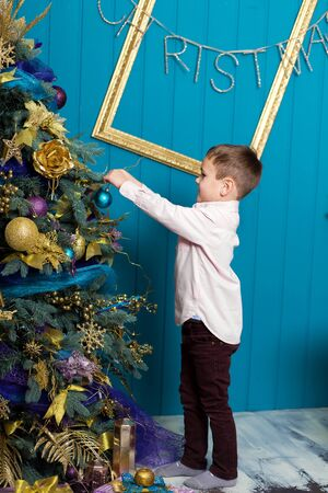 Cute little boy decorating christmas tree. Young kid in light bedroom with winter decoration. Happy family at home. Christmas New Year december time for celebration concept. Stock Photo