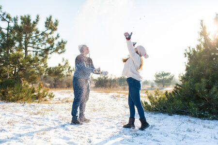 Loving couple play snowballs in winter in the forest. Throw each other snow. Laugh and have a good time. Stock Photo