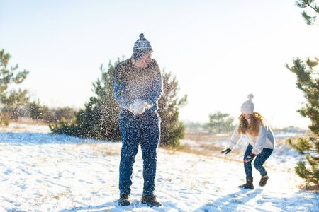 Loving couple play snowballs in winter in the forest. Throw each other snow. Laugh and have a good time.