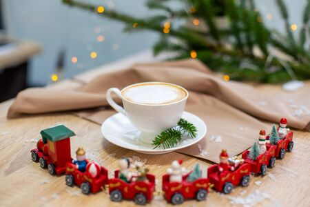 Delicious fresh festive morning cappuccino coffee in a ceramic white cup on the wooden table with decorative christmas train, red ornamentals, fireflies and spruce branches. Stock Photo