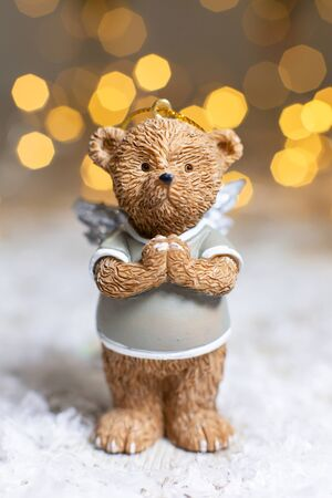 Decorative figurines of a Christmas theme. Figurine of a cute bear with angel wings. Festive decor, warm bokeh lights. Stok Fotoğraf