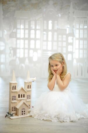 little girl in a white dress plays in a big white toy city.