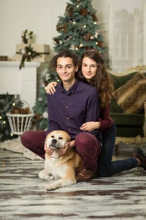 Young happy couple cuddling with a dog sitting on the floor near the Christmas tree. Stock Photo