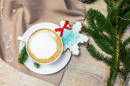 Christmas and happy new year card with cup of coffee, pine, fir branch and gingerbread on wooden table background, copy space, top view. Stock Photo