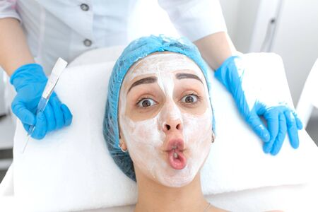 Woman professional doctor beautician applies a mask on a patients face for skin care. Cosmetic procedures for skin rejuvenation and nutrition.