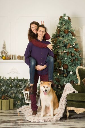 A young couple with a dog fooling around near a Christmas tree. Happy new year and merry christmas.