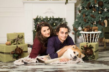 Young happy couple cuddling adorable akita inu dog with on the floor for Christmas holidays at home Stock Photo