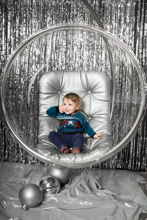 Little boy plays in a chair a glass bowl with silver balls. Фото со стока