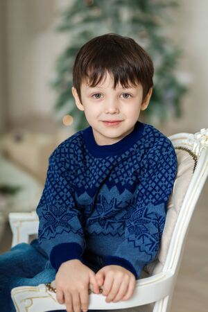 Happy little smiling boy sitting on armchair near christmas tree and holding christmas gift box Фото со стока