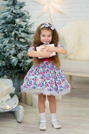 little girl with a big Christmas present poses near the Christmas tree.