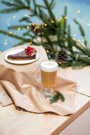 Delicious fresh festive morning cappuccino coffee in a glass cup and cupcake dessert on the wooden table, fireflies and spruce branches.