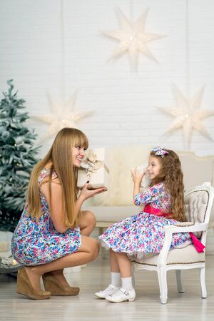 little girl with a big Christmas present together with mom poses near the Christmas tree