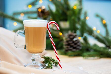 Delicious cappuccino coffee cup and Christmas candy sweet. fireflies and spruce branches background