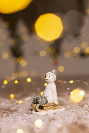 Decorative Christmas-themed figurines. The statuette of a polar bear sits on a wooden sled, in a knitted hat and socks. Christmas tree decoration. Festive decor, warm bokeh lights