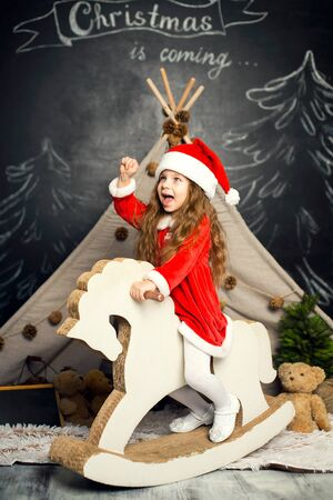 Little girl in Santa costume on a rocking horse is ready to celebrate the holidays. Фото со стока