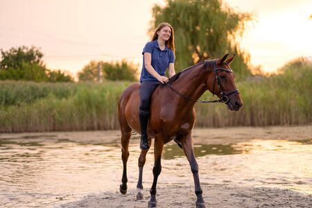 A young girl riding a horse on a shallow lake. A horse runs on water at sunset. Care and walk with the horse. Strength and Beauty. Stock fotó